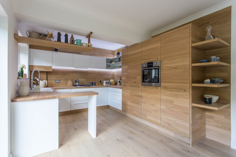 Scandinavian style kitchen with white doors and oak details. Bespoke White and oak kitchen