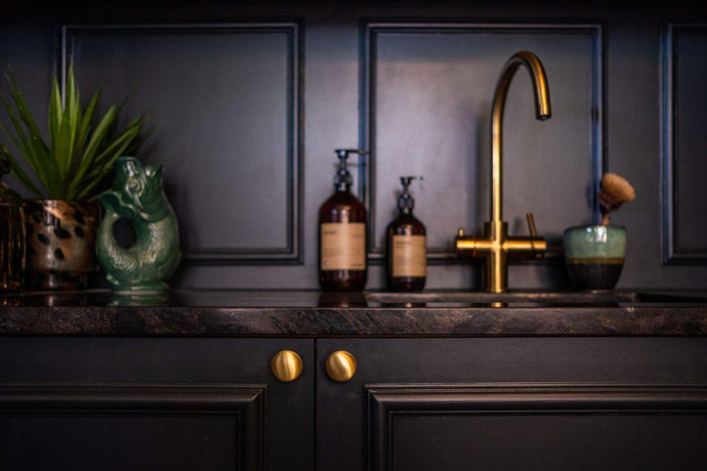 Dark panelled kitchen , gold taps